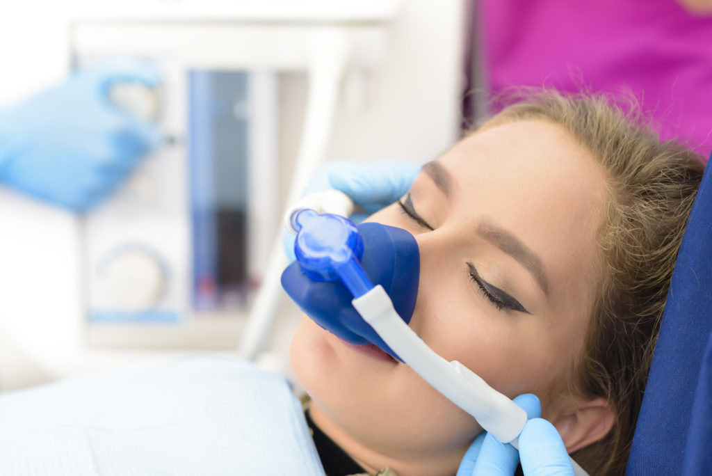Image of a patient with a nose mask receiving laughing gas to relieve anxiety at McQueen Dental in Fayetteville, AR.
